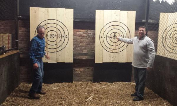 Two people stand in a shooting gallery pointing excitedly at a target