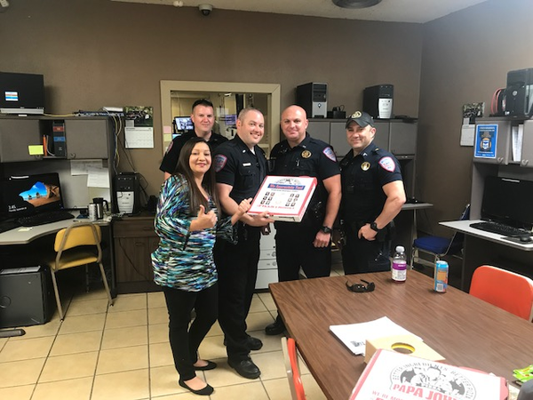 Police officers pose with a donated pizza