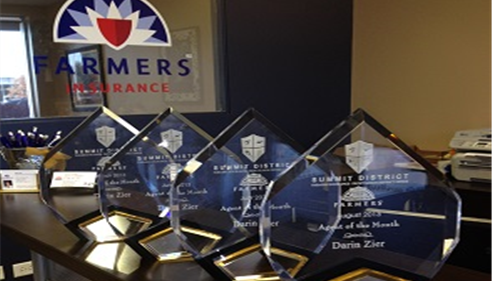 Summit District Agent of the Month awards on a desk with the Farmers logo in the background