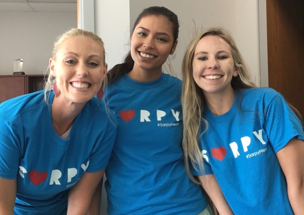 Three women pose in matching t-shirts