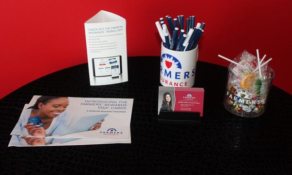 A table in Agent Monika Spadlo's office, with business cards, plus Farmers Insurance promotional and informational materials on it.