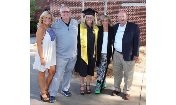 A photo of four adults posing with a student who graduated college.