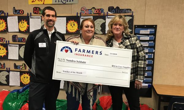 Agent standing in classroom with two teachers holding a large check