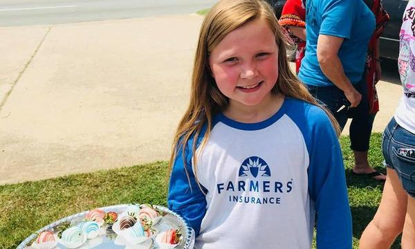young girl in a farmers tshirt serving treats.