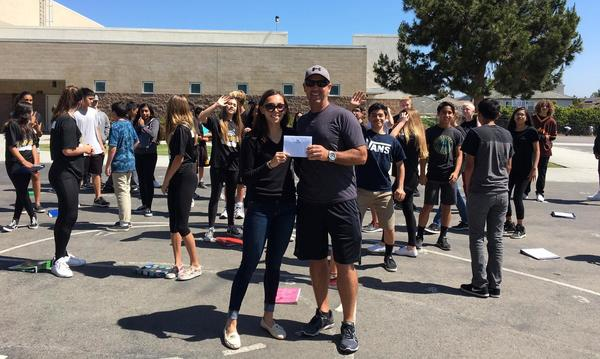 female and male holding envelope with a diverse group of students in black scattered in the background.