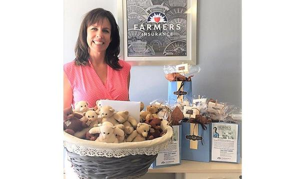 Agent Marilyn Furbush standing with a basket of teddy bears in her office.