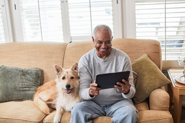 Senior man using tablet on couch with dog