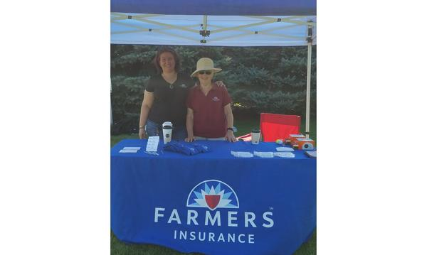 A woman puts her arm around a woman in a sun hat outside at a Farmers booth