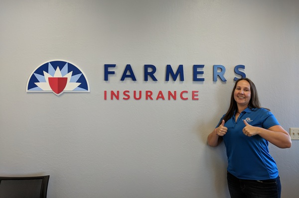amy giving thumbs up beside farmers logo
