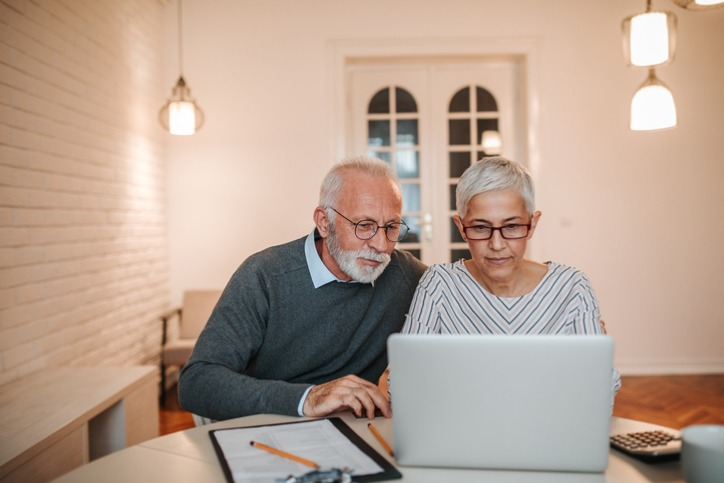 older couple doing research on their laptop