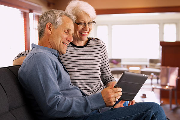 A happy man and woman looking at a tablet