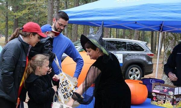 Agent Ruth dressed as a witch handing out candy to trick or treaters.