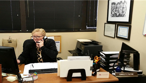 A man sits at a desk speaking on the phone