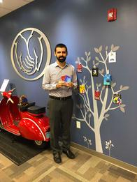 "John Lofrumento standing in front of his office ""referral tree"" of gift cards"