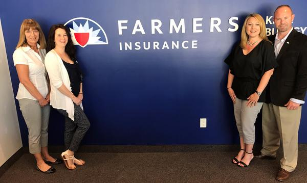 Agent Danielle and 3 staff members by blue wall with Farmers logo