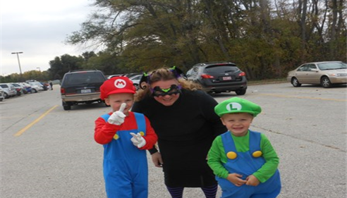 Woman and two boys in costumes.