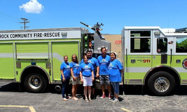 A group of six adults posing in front of a Fire truck.
