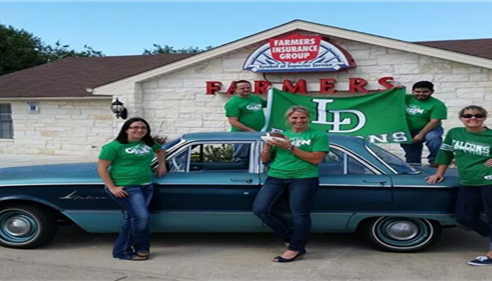Five adults posing with a car in front of the Farmers agency.
