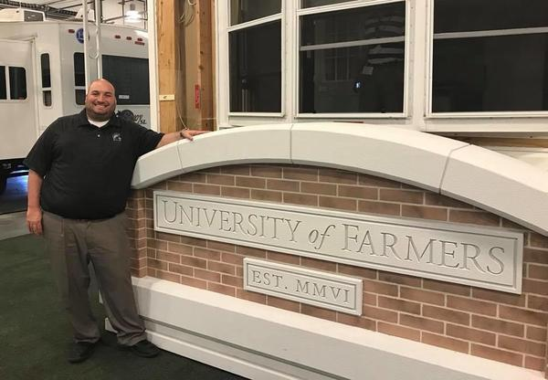 Photo of agent by university of farmers sign