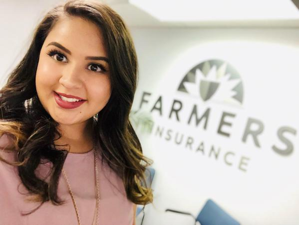 A photo of Yesenia, one of agent Ronald William's staff members, in front of the Farmers Insurance logo.