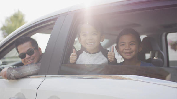 Family sitting in a car looking out the window and smiling