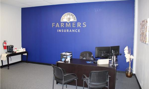 An office with a Farmers Logo on the wall and a desk in the corner