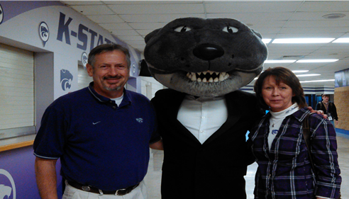 Agent standing with wife and Kansas State University Mascot