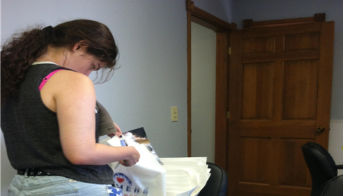 A person working with Farmers Insurance bags.