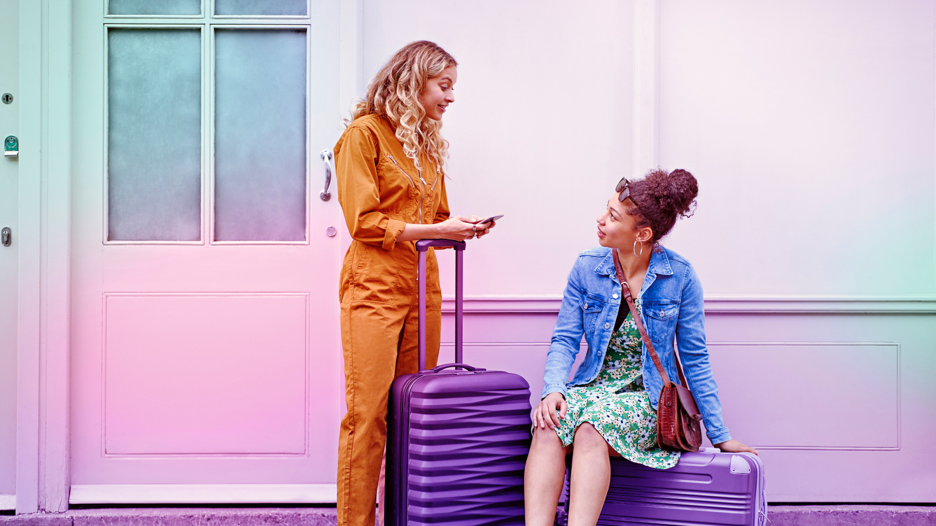 One woman sits on top of a suitcase and another woman leans on the extended handle of another suitcase while she uses her Three Mobile network on her phone.