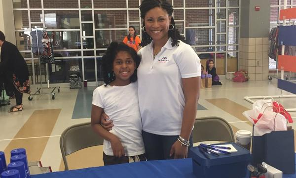 Agent Michel Hambrick with a young girl at a Farmers booth for a local school's fundraiser.