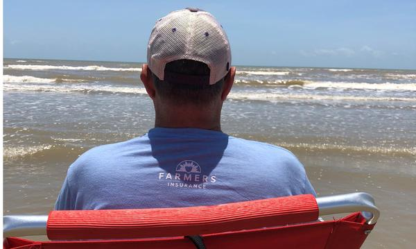Photo of a man wearing a Farmers shirt looking at the ocean water.