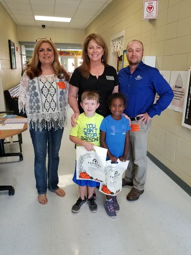 Farmers agent posing with teachers and students at the Altamaha Elementary School