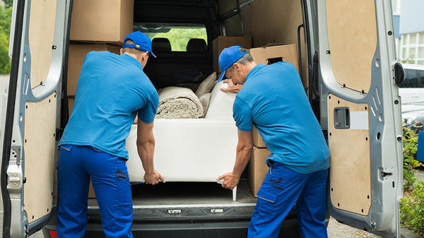 two men moving couch into moving van