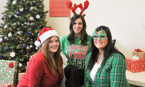 Agent and two female staff members standing in front of a christmas tree wearing christmas themed clothing