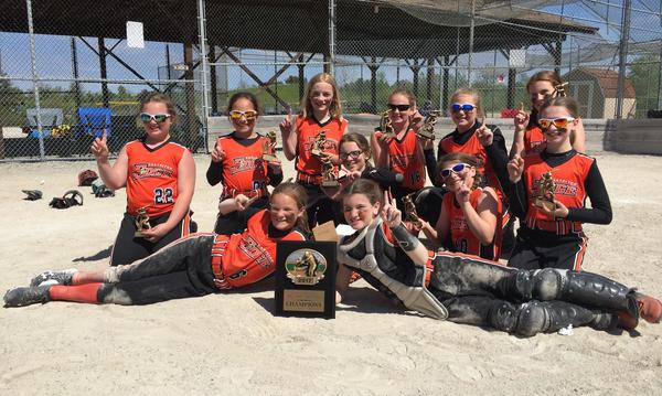 girls' softball team smiles while holding plaque