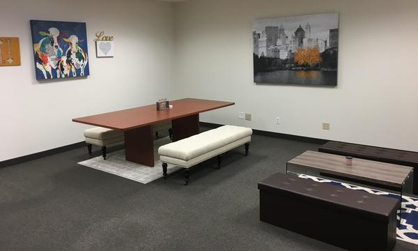 A conference table and couch inside of the Eric Choi Agency.