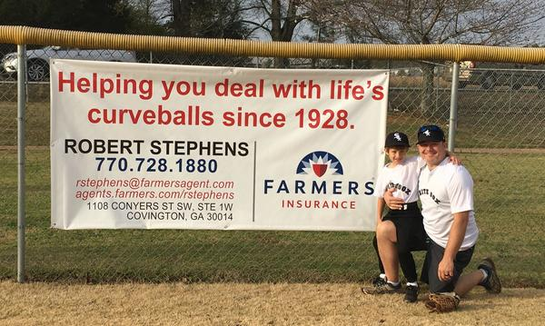 "Agent Robert Stephens with his son, standing next to a sign on the fence of a baseball field that reads, ""Helping you deal with life's curveball's since 1928."""