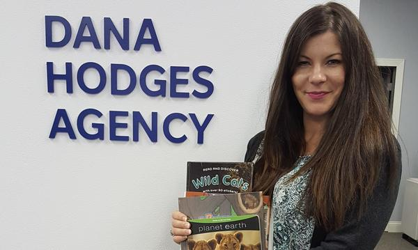 The agent is holding children books and standing next to a sign that says her own name