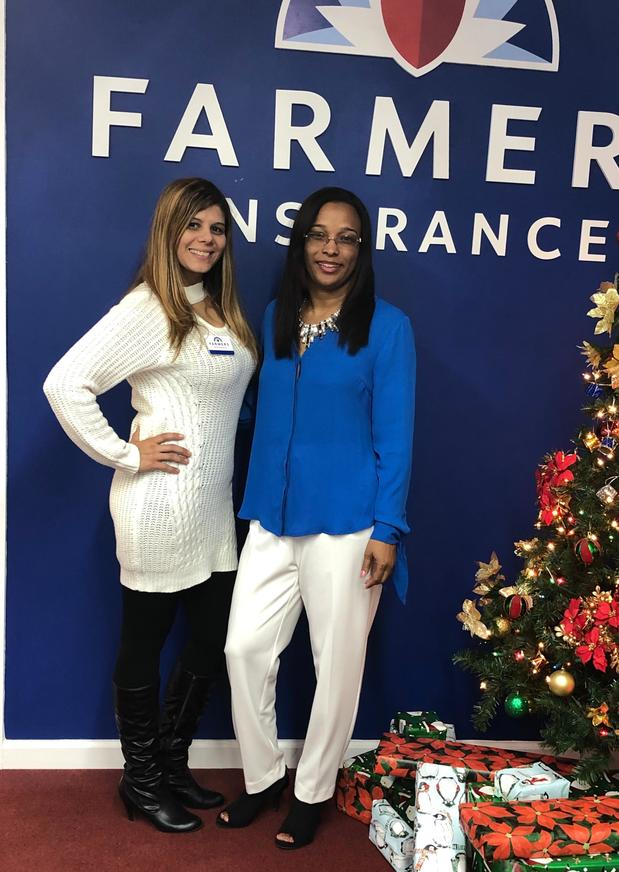 Two women standing in front of a Farmers® Insurance sign