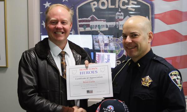 John presents an award to a local police officer