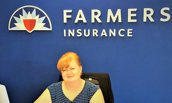 Woman sitting in chair in front of Farmers logo