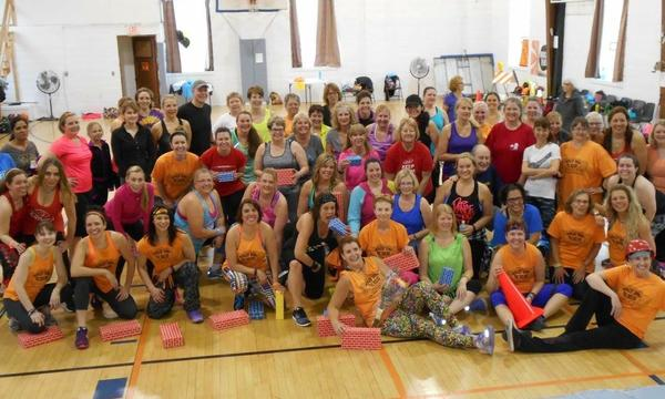A large group of zumba enthusiasts sit in a gym