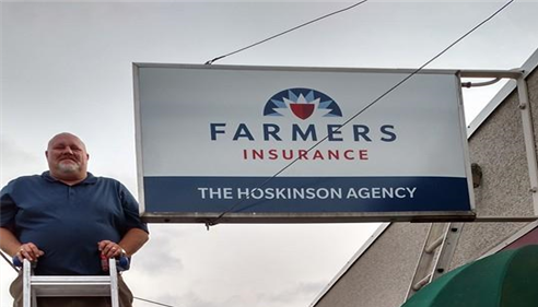 agent next to farmers sign