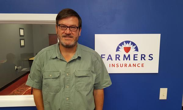 Michael Benham Agency staff member, Rip West, in green collared shirt next to the Farmers logo on a blue wall.