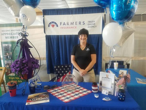 "A woman wearing a Farmers Insurance polo stands at a Farmers Insurance table. Behind her, a sign reads, ""Farmers Insurance: Trudy Grove Agency."""