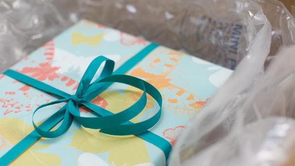 Gift with teal bow packed in box with inflatable air cushioning