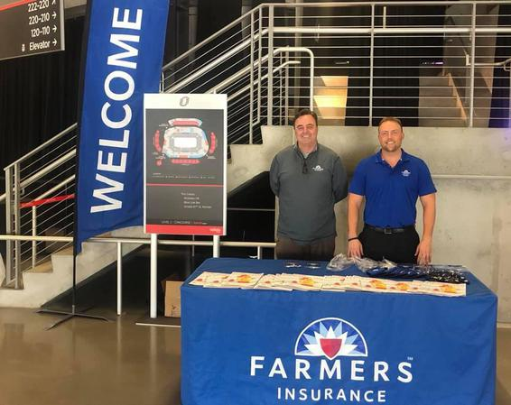 two men behind a farmers insurance booth