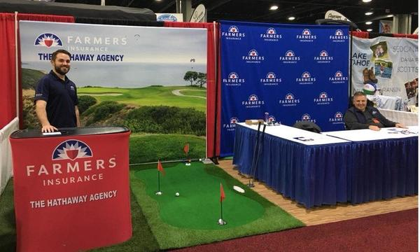 Agent standing behind Farmers booth with a small putting green
