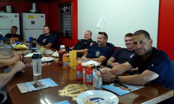 A group of firemen sitting at a table smiling