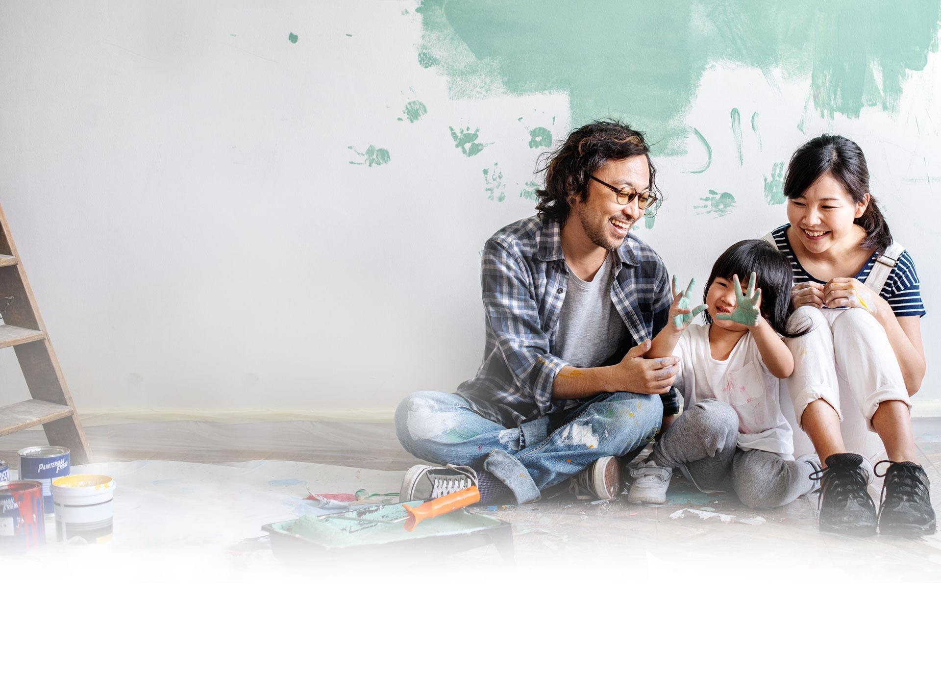Photo of a smiling family sitting on the floor of a new home, their small child has put handprints on the wall with wet paint